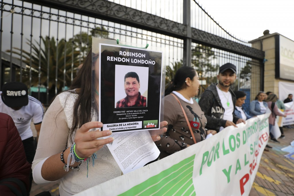 A woman holds a sign with a man's photo that say  he disappeared in 2015, as she attends an anti-government protest outside the National Center for Hi...