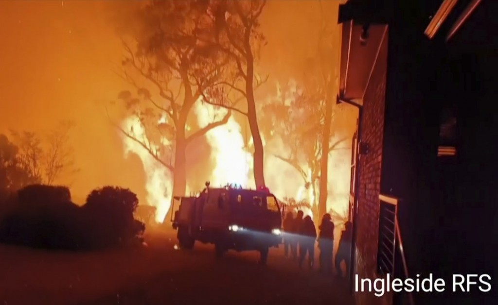 This image made from video taken on Dec. 22, 2019, and provided Dec. 25, 2019, by Ingleside Rural Fire Brigade, shows the wildfire behind an emergency...