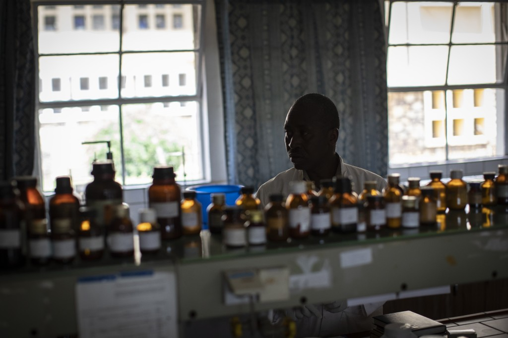 In this photo taken Thursday, Nov. 7, 2019, biochemist Denys Rukarata works in the room where he tests locally-produced oral liquid morphine for purit...