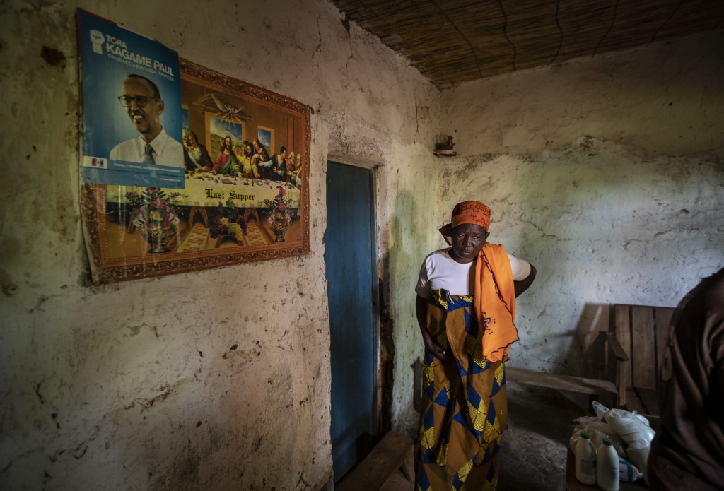 In this photo taken Tuesday, Nov. 5, 2019, Faina Nyirabaguiza, 52, who has cervical cancer, walks slowly and in pain back to her bedroom after being g...