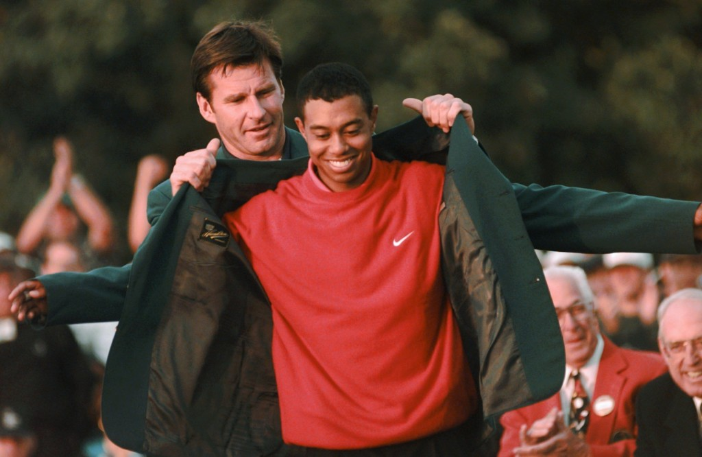 FILE - In this April 13, 1997 file photo, Masters champion Tiger Woods receives his Green Jacket from last year's winner Nick Faldo, rear, at the Augu...