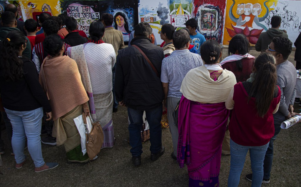 People watch the displayed works by Indian artist at an event organized by a students organization to protest against a new citizenship law that oppon...
