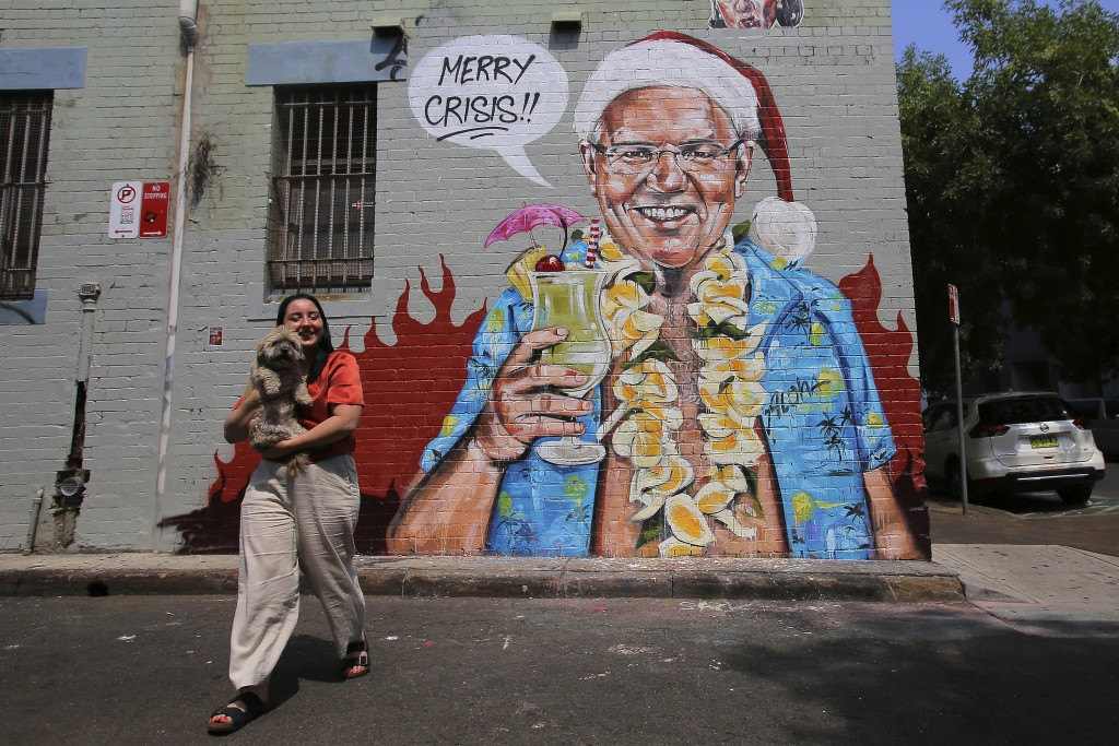 A mural depicting Prime Minister Scott Morrison wearing an unbuttoned Hawaiian shirt, orange lei and Santa Claus hat while holding a cocktail by artis...
