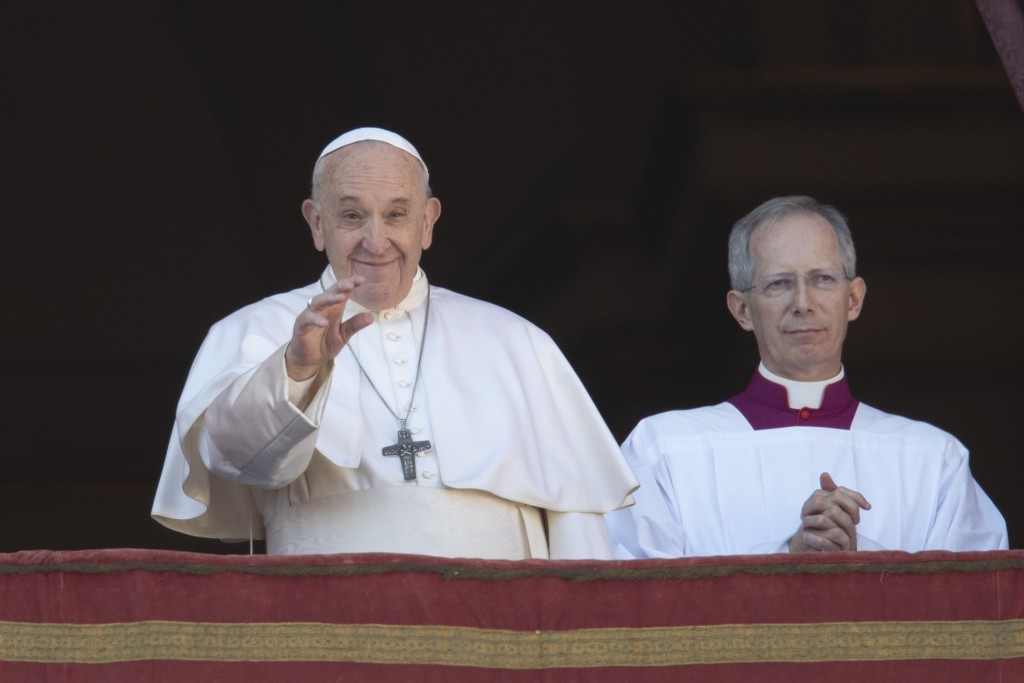 Pope Francis, flanked by Mons. Guido Marini, the Vatican master of liturgical ceremonies, waves to faithful and pilgrims after he delivered the Urbi e...