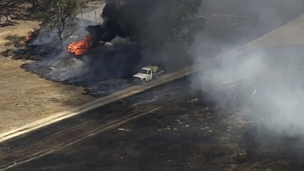 In this image made from video, an aerial scene shows a truck driving near fire burning in Harrogate, South Australia, Wednesday, Dec. 25, 2019.  South...