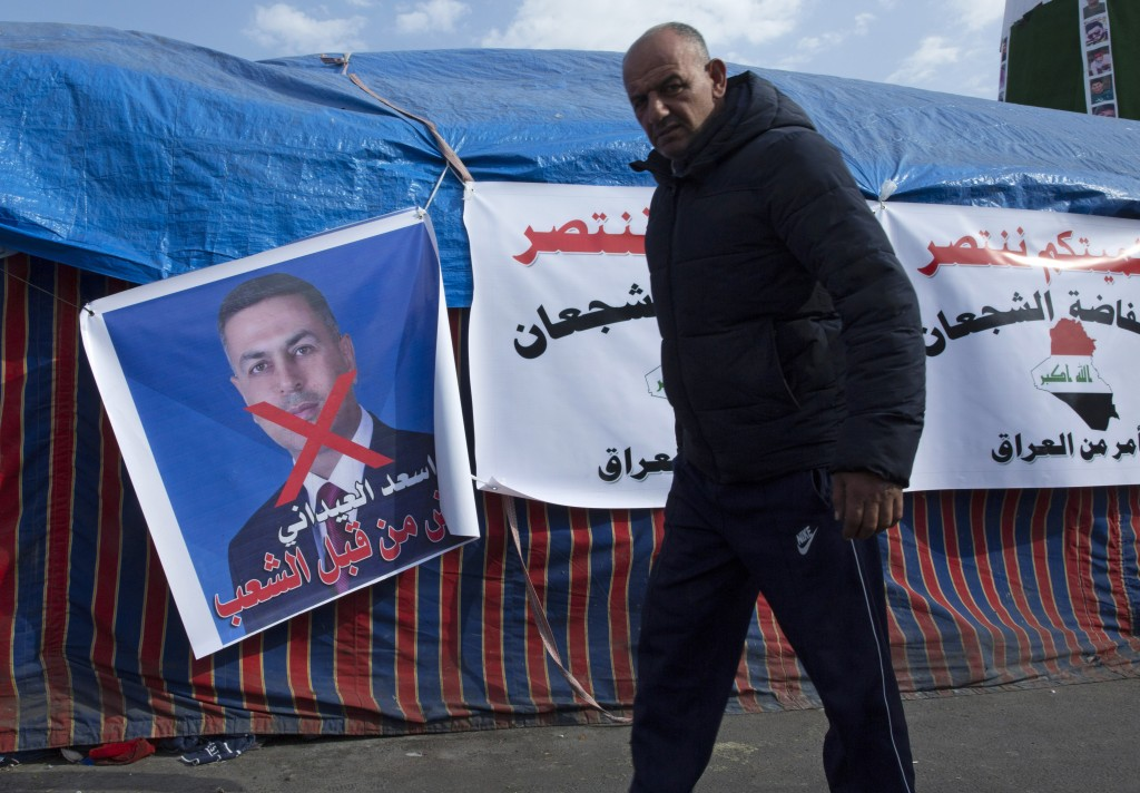"""A protester walks past a poster with a defaced picture of the governor of the southern Basra province Asaad al-Eidani and Arabic that reads """"rejected ..."""