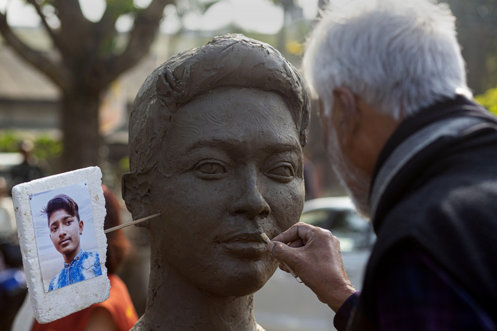 Indian sculptor Biren Singha makes a sculpture of Dipanjal Das, who was killed in police firing earlier this month, at an event organized by a student...