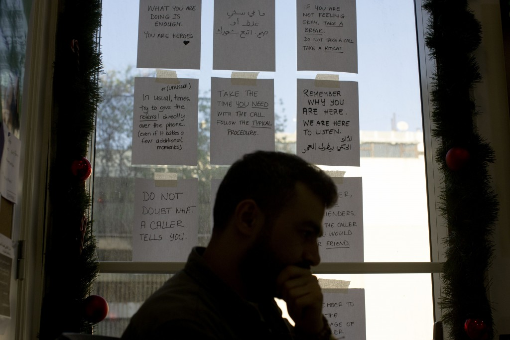 In this Monday, Dec. 23, 2019 photo, words of encouragement are taped to a window next to Bassem, a volunteer, as he waits for calls at at Lebanon's E...