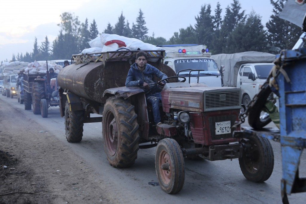 A man pulls a tanker trailer as civilians flee a Syrian military offensive in Idlib province on the main road near Hazano, Syria, Tuesday, Dec. 24, 20...