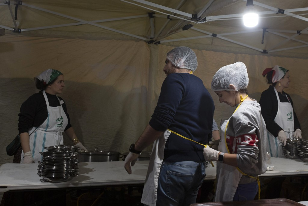 In this Monday, Dec. 23, 2019, photo, a woman ties an apron on a fellow volunteer before they serve a public Christmas dinner for the needy in Martyrs...