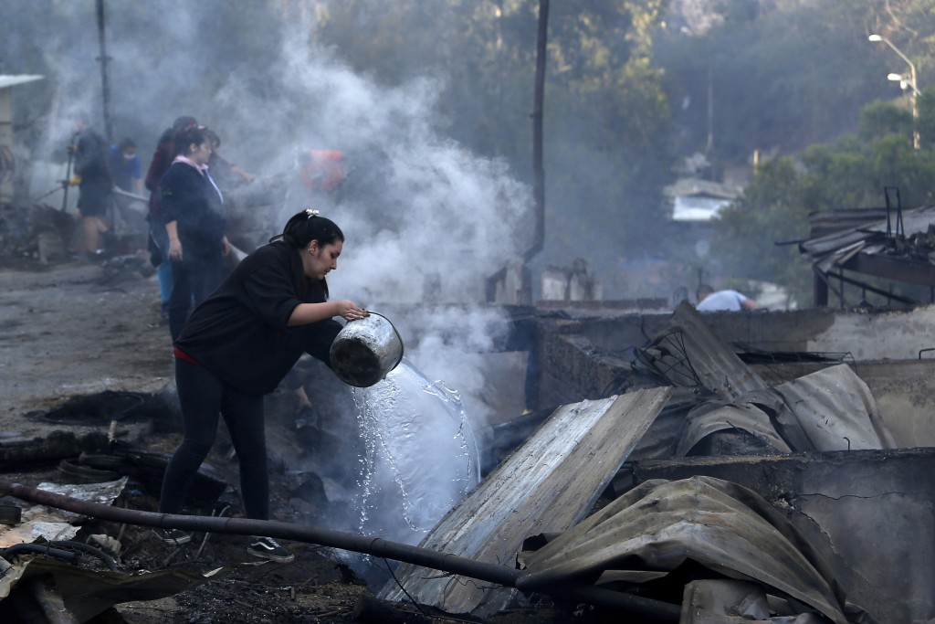 Residents spray water over remains of their homes after a wildfire damaged dozens of houses on the outskirts of Valparaiso, Chile, Wednesday, Dec. 25,...