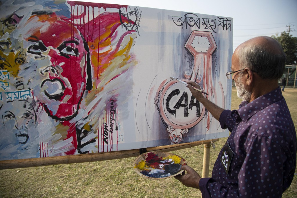 An Indian artist paints on a canvas at an event organized by a students organization to protest against a new citizenship law that opponents say threa...