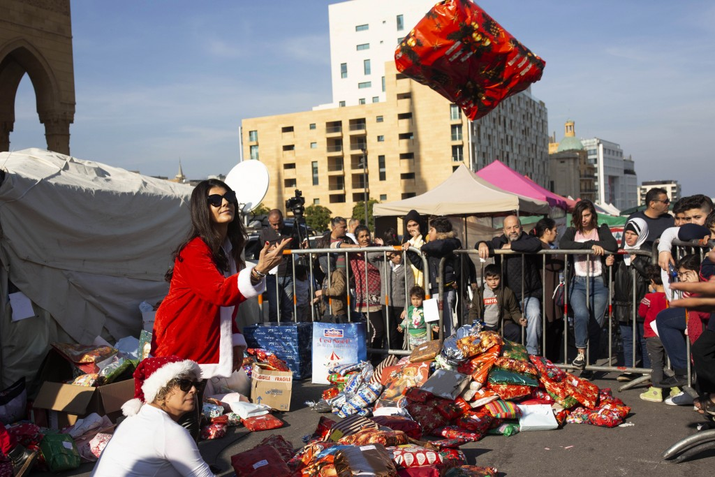 In this Sunday, Dec. 22, 2019, photo, volunteer Ibtisam Nablussi tosses a Christmas present, as anti-government protesters distribute clothing to the ...