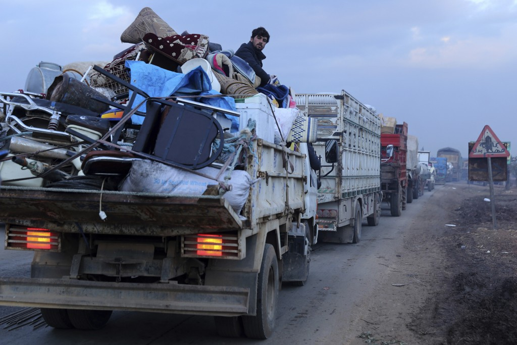A man rides in a truck as civilians flee a Syrian military offensive in Idlib province on the main road near Hazano, Syria, Tuesday, Dec. 24, 2019. Sy...