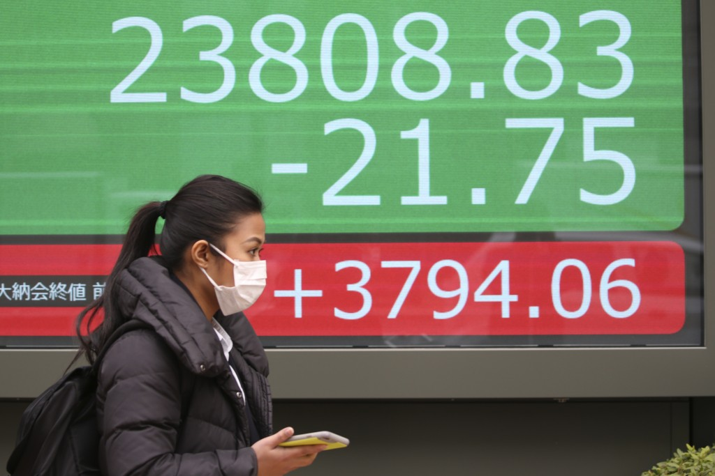 A woman walks by an electronic stock board of a securities firm in Tokyo, Wednesday, Dec. 25, 2019. Chinese and Japanese stocks declined Wednesday whi...
