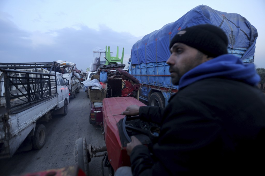 Civilians flee a Syrian military offensive in Idlib province on the main road near Hazano, Syria, Tuesday, Dec. 24, 2019. Syrian forces launched a wid...