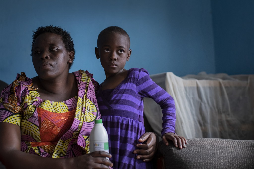 In this photo taken Wednesday, Nov. 6, 2019, mother Joselyne Mukanyabyenda, left, holds the bottle of oral liquid morphine that her daughter Ange Mucy...