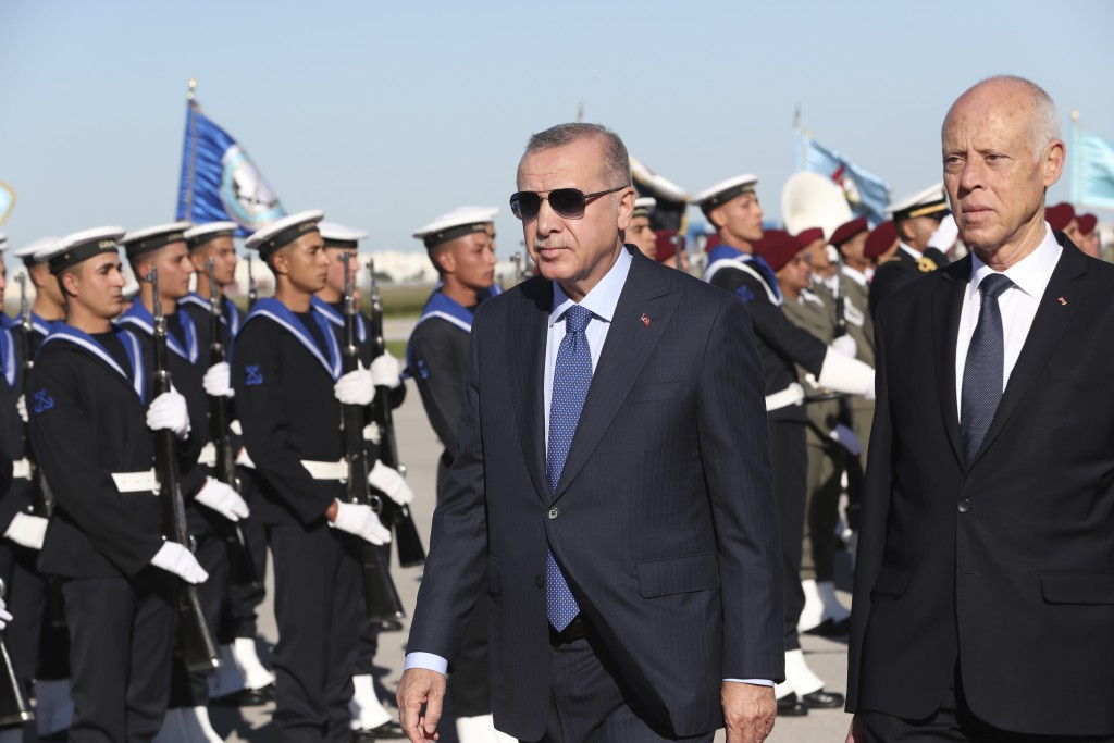 Turkey's President Recep Tayyip Erdogan, left, and Tunisian President Kais Saied review a honor guard at the airport, in Tunis, Tunisia, Wednesday, De...