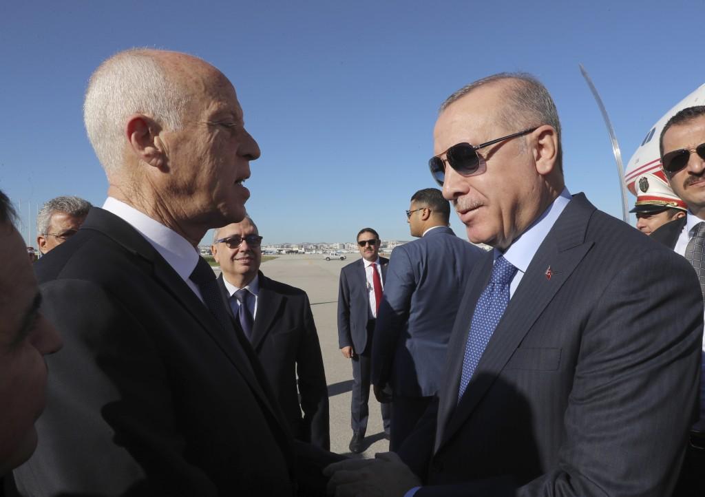 Turkey's President Recep Tayyip Erdogan, right, and Tunisian President Kais Saied, speak as they meet at the airport, in Tunis, Tunisia, Wednesday, De...