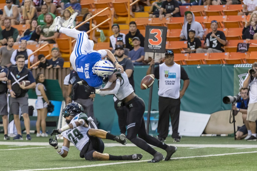 BYU quarterback Zach Wilson (1) loses the football on a hit by Hawaii defensive back Eugene Ford, right, as Wilson tried to leap into the end zone dur...