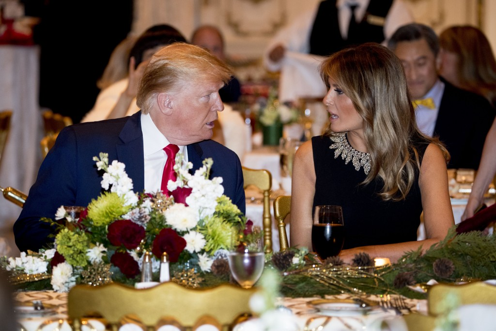 President Donald Trump and first lady Melania Trump talk at Mar-a-lago while there for Christmas Eve dinner in Palm Beach, Fla., Tuesday, Dec. 24, 201...