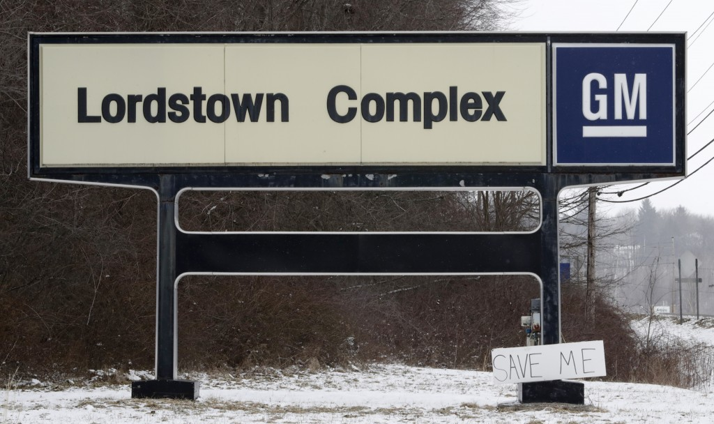 """FILE - In this March 6, 2019 file photo, A """"Save Me"""" sign rests against the Lordstown Complex sign in Lordstown, Ohio.  The long-struggling Rust Belt ..."""