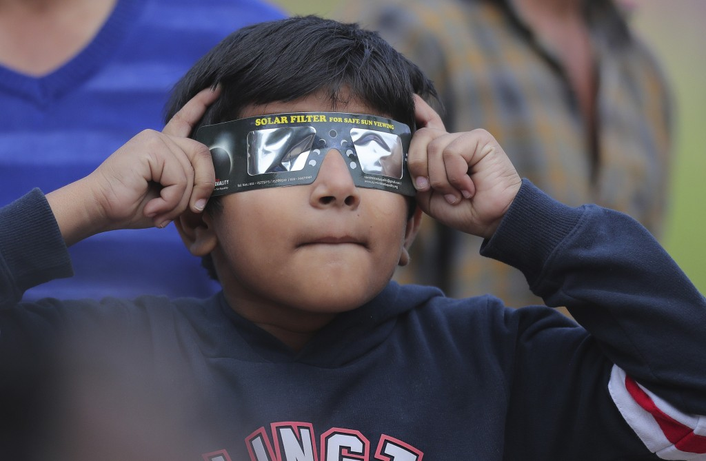 A boy holds a special filter and watches a partial solar eclipse in Hyderabad, India, Thursday, Dec. 26, 2019. (AP Photo/Mahesh Kumar A.)