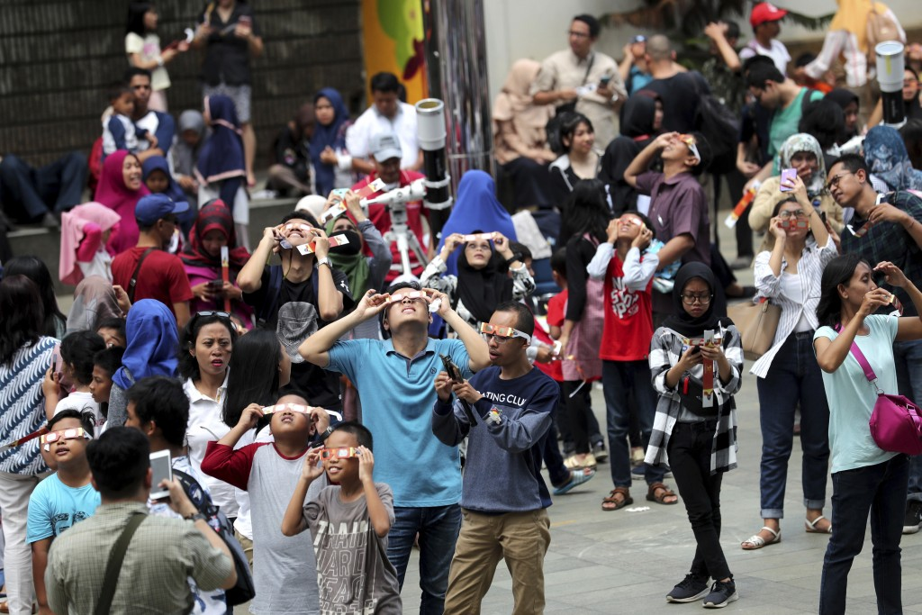 People look up at the sun with protective glasses to watch a solar eclipse from Jakarta, Indonesia, Thursday, Dec. 26, 2019. (AP Photo/Tatan Syuflana)