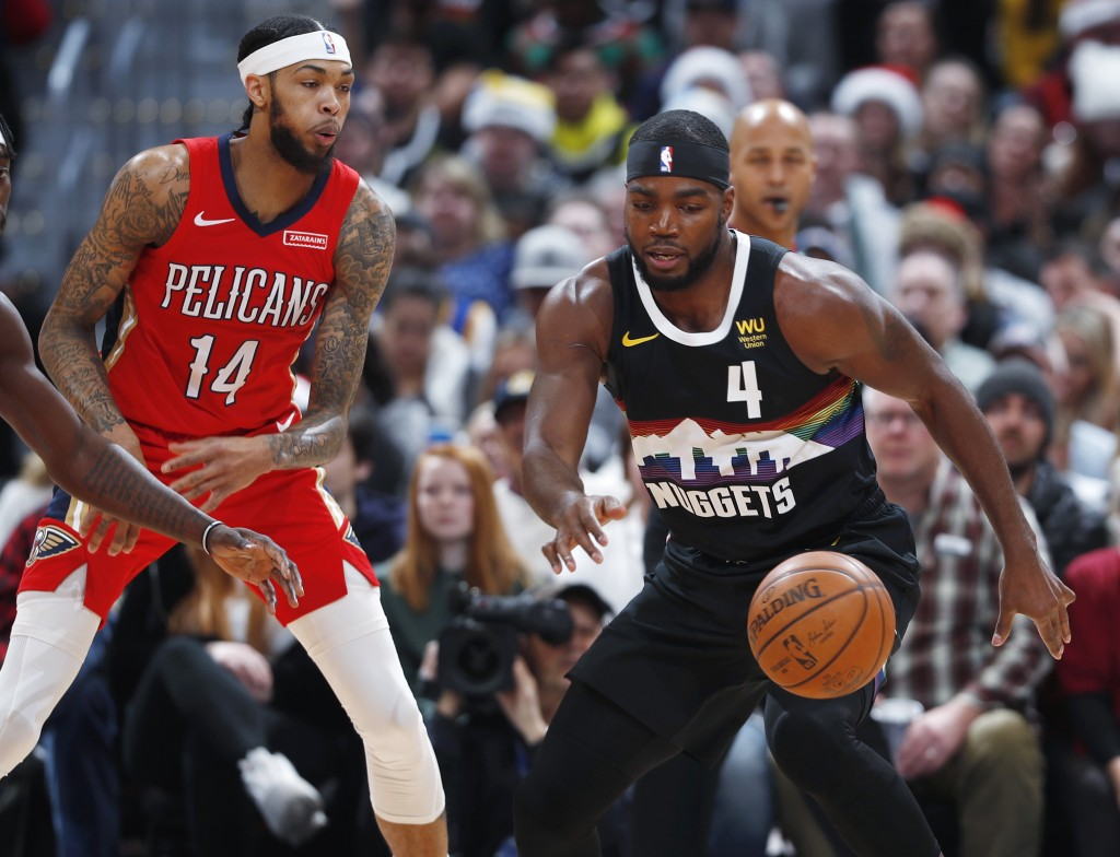 Denver Nuggets forward Paul Millsap, right, loses control of the ball as New Orleans Pelicans forward Brandon Ingram defends during the first half of ...