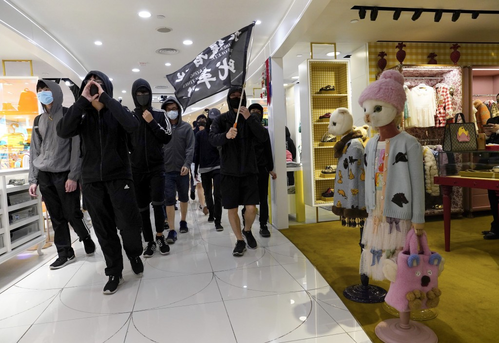 """Protesters carry a flag reading """"Liberate Hong Kong, the Revolution of Our Times"""" as they march through a shopping mall in Causeway Bay in Hong Kong, ..."""