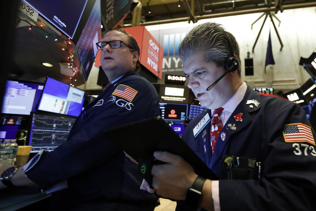 FILE - In this Dec. 13, 2019, file photo specialist Gregg Maloney, left, and trader John Panin work on the floor of the New York Stock Exchange. The U...