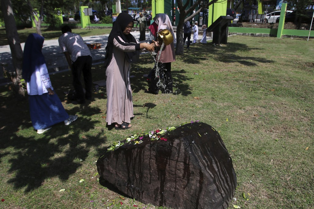 A woman pours water at a stone marking the mass grave for the victims of the Indian Ocean tsunami following prayers commemorating the 15th anniversary...