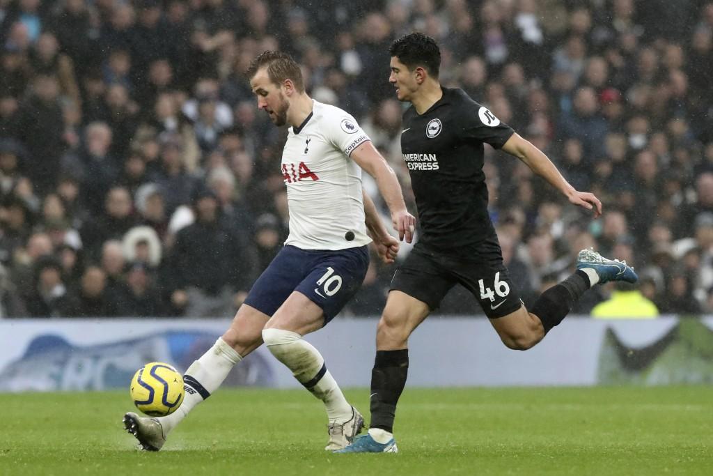 Tottenham's Harry Kane kicks the ball next to Brighton's Steven Alzate, right, during the English Premier League soccer match between Tottenham Hotspu...