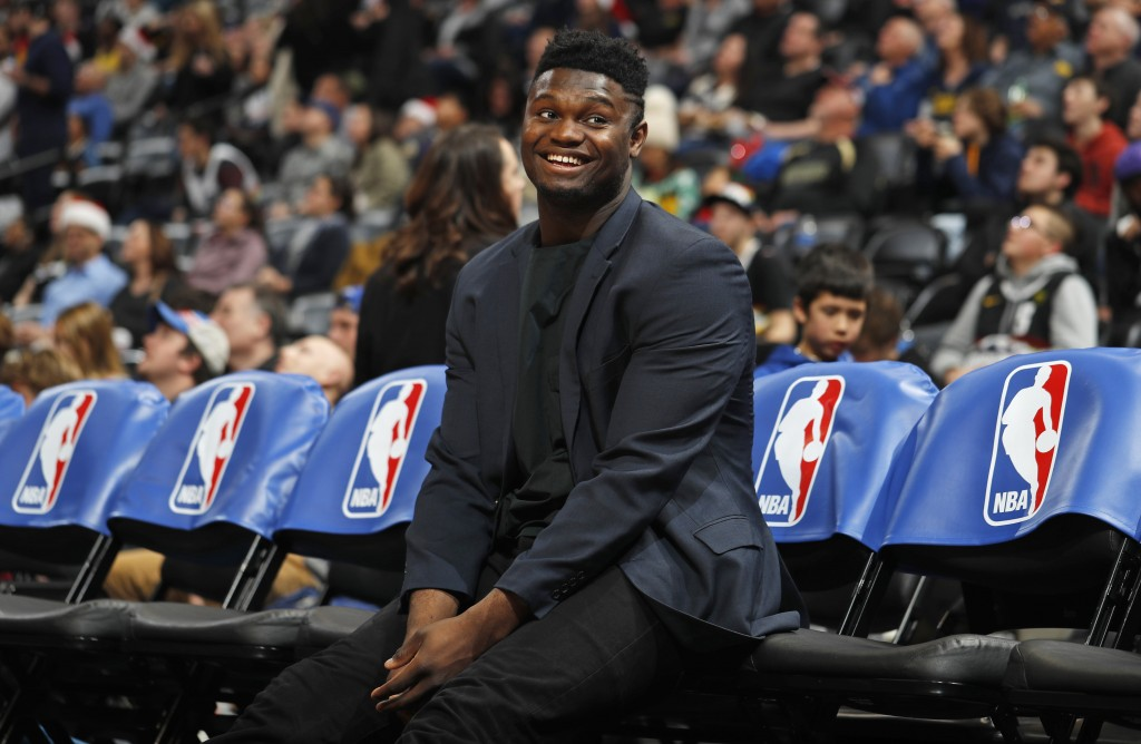 Injured New Orleans Pelicans forward Zion Williamson smiles as he jokes with fans while waiting on the team bench for the second half of the team's NB...