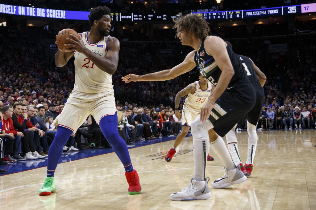 Philadelphia 76ers' Joel Embiid, left, looks to make his move on Milwaukee Bucks' Robin Lopez, right, during the first half of an NBA basketball game,...