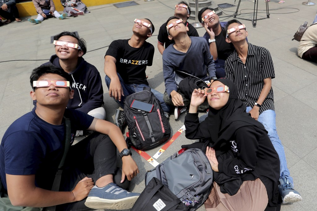 People look up at the sun wearing protective glasses to watch a solar eclipse in Jakarta, Indonesia, Thursday, Dec. 26, 2019. (AP Photo/Tatan Syuflana...
