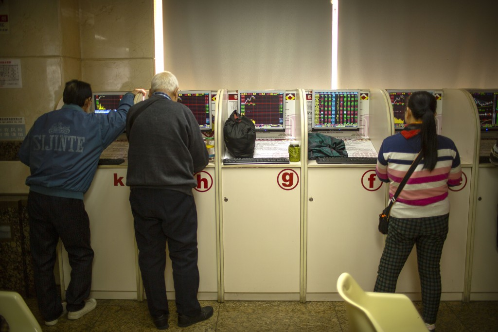 Chinese investors use computer terminals as they monitor stock prices at a brokerage house in Bejiing, Thursday, Dec. 26, 2019. Shares are mostly high...