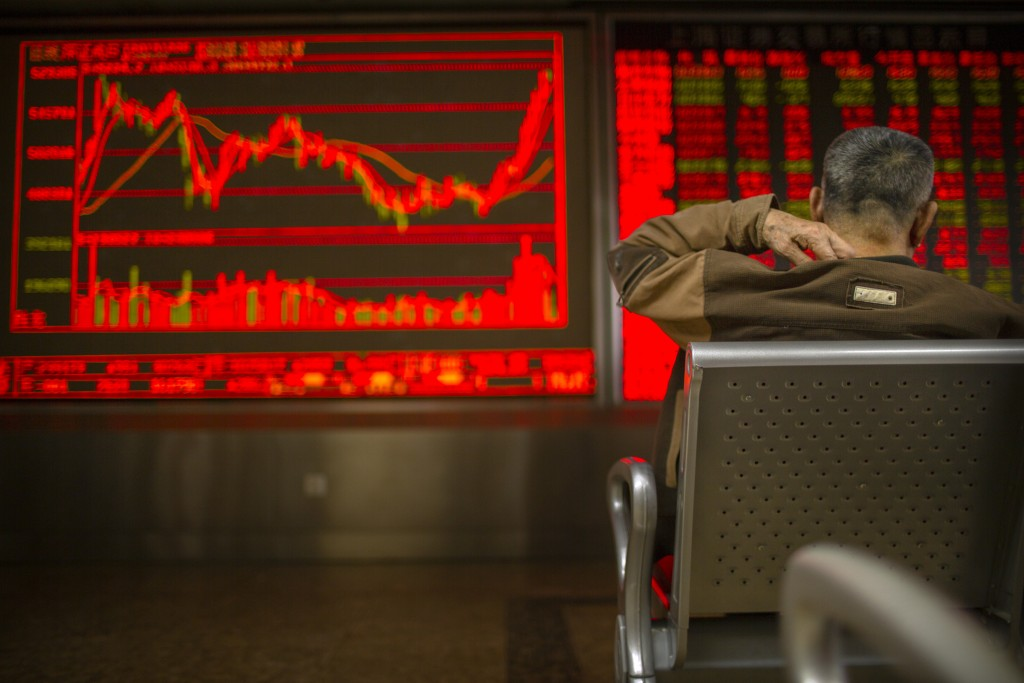 A Chinese investor monitors stock prices at a brokerage house in Bejiing, Thursday, Dec. 26, 2019. Shares are mostly higher in Asia with many world ma...
