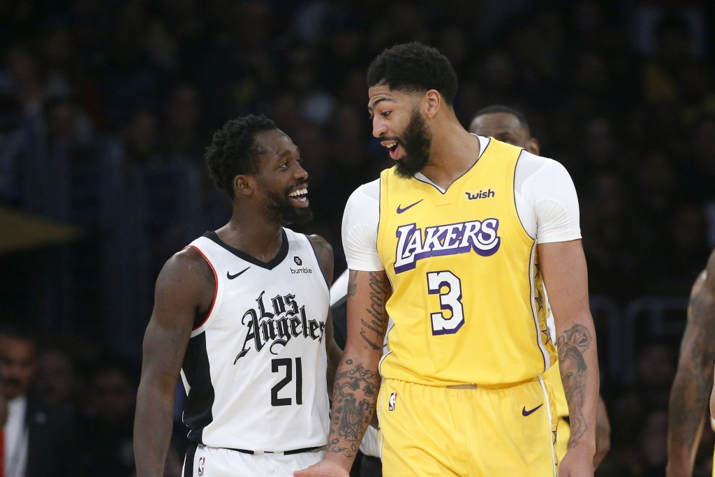 Los Angeles Lakers' Anthony Davis (3) talks with Los Angeles Clippers' Patrick Beverley (21) during the first half of an NBA basketball game Wednesday...