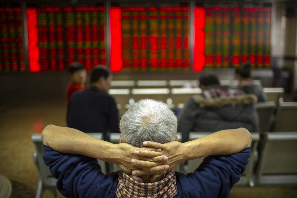Chinese investors monitor stock prices at a brokerage house in Bejiing, Thursday, Dec. 26, 2019. Shares are mostly higher in Asia with many world mark...