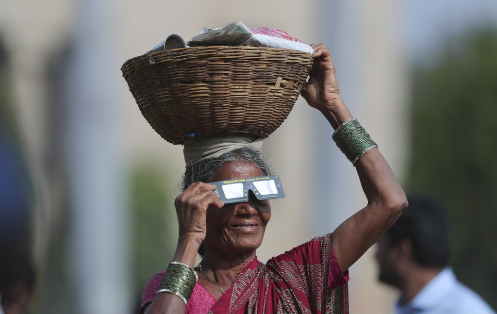 In this Thursday, Dec. 26, 2019, file photo, a roadside vendor holds a special filter and watches a partial solar eclipse in Hyderabad, India, Thursda...