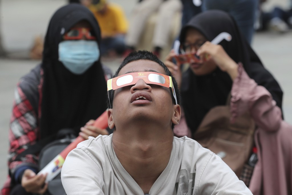 People look up at the sun wearing protective glasses to watch a solar eclipse from Jakarta, Indonesia, Thursday, Dec. 26, 2019. (AP Photo/Tatan Syufla...