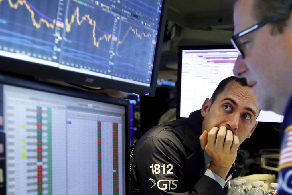 FILE - In this Nov. 14, 2019, file photo a pair of specialists work on the floor of the New York Stock Exchange. Investments around the world were all...
