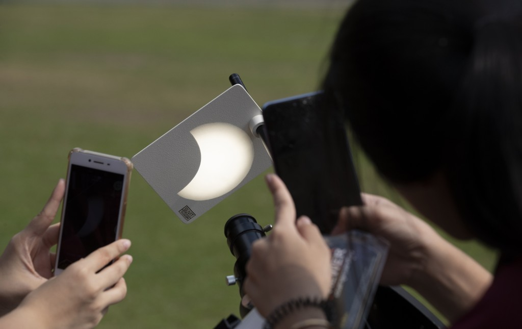 Students take a picture of a reflection of a partial solar eclipse at a school in Bangkok, Thailand, Thursday, Dec. 26, 2019. (AP Photo/Sakchai Lalit)