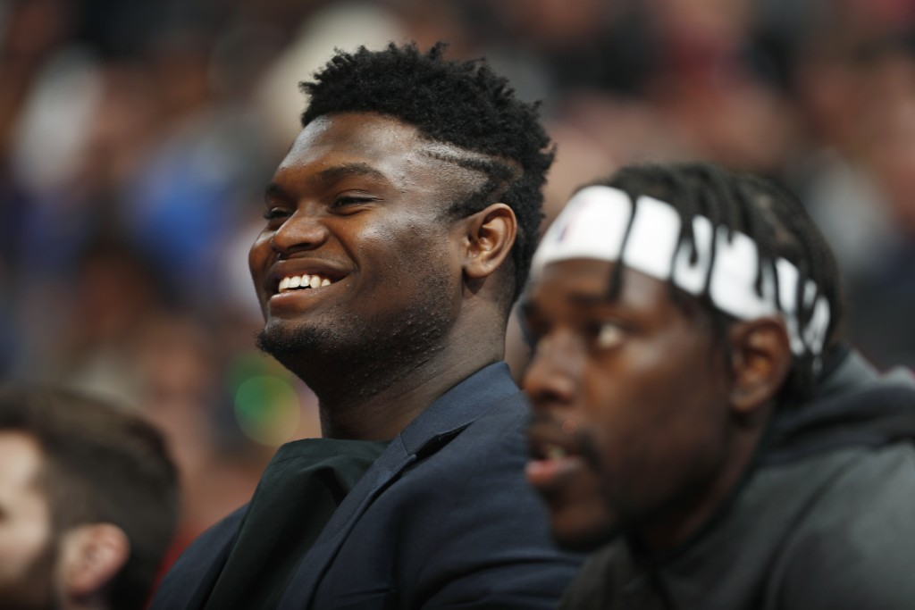 Injured New Orleans Pelicans forward Zion Williamson, left, and guard Jrue Holiday watch from the bench during the second half of the team's NBA baske...