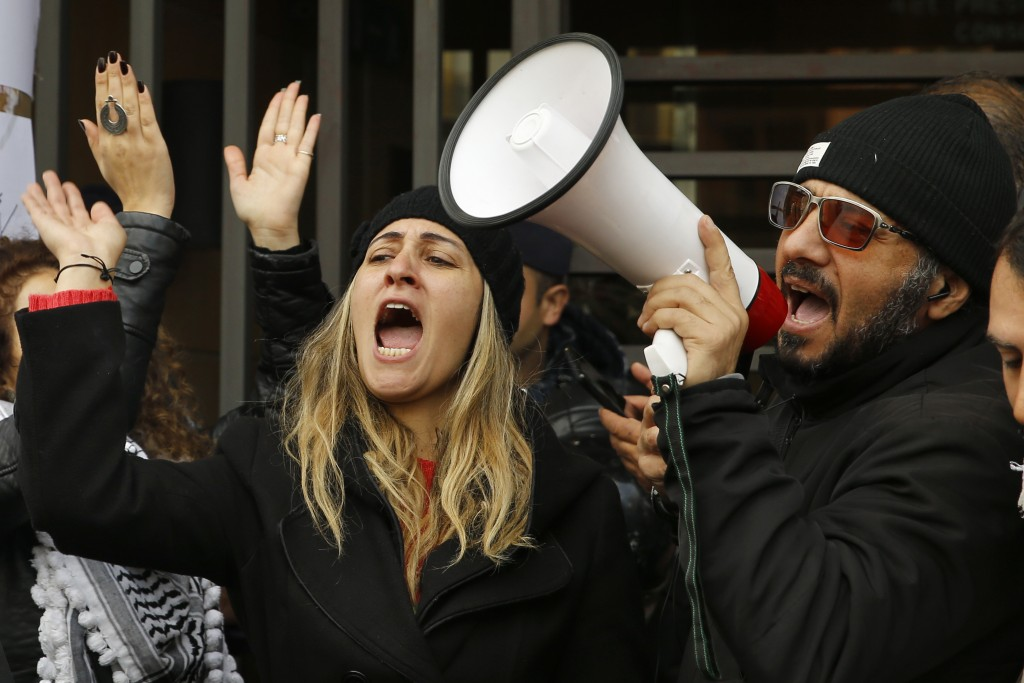 Protesters chant slogans during ongoing protests against the Lebanese political class, in front of the building of the Lebanese Association of Banks i...