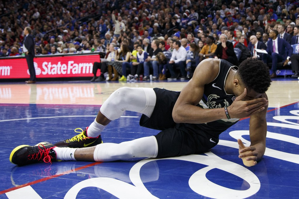 Milwaukee Bucks' Giannis Antetokounmpo lays on the court after getting poked in the eye during the second half of an NBA basketball game against the P...
