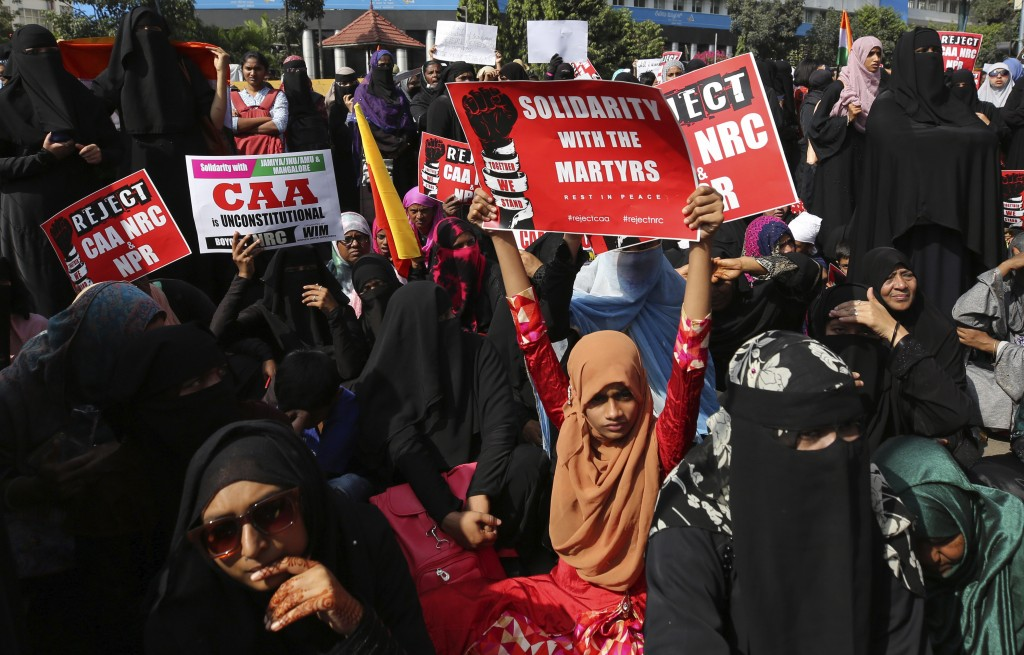 Indians hold placards during a protest against a new citizenship law that opponents say threatens India's secular identity in Bangalore, India, Thursd...