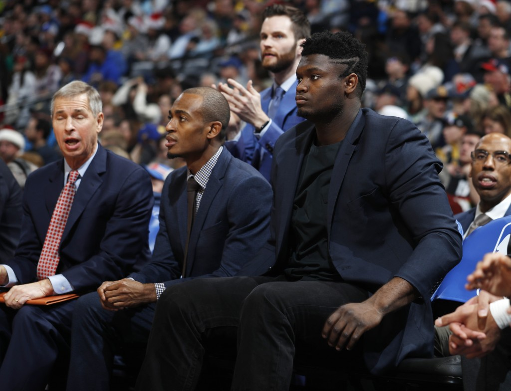 Injured New Orleans Pelicans forward Zion Williamson, right, sits on the team bench during the first half of the Nuggets' NBA basketball game against ...