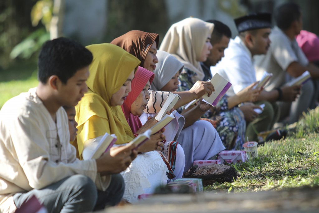 In this Thursday, Dec. 26, 2019, file photo, people read the holy book of the Quran as they pray at a mass grave site for the victims of the Indian Oc...